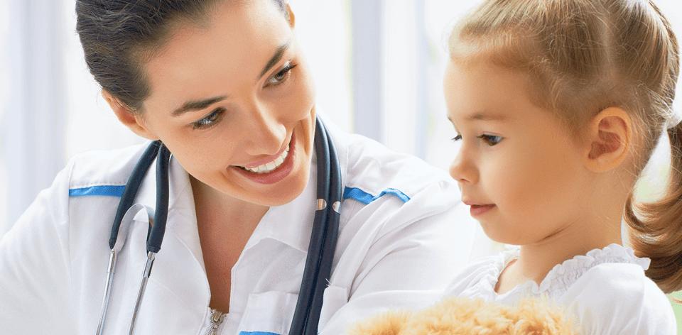 uśmiechnięta lekarka z małą dziewczynką