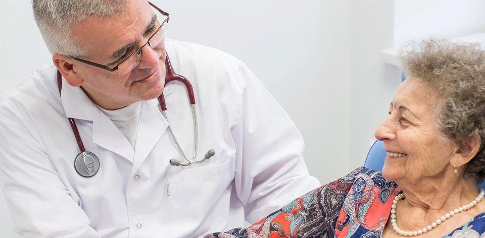 uśmiechnięty lekarz rozmawiający ze starszą pacjentką