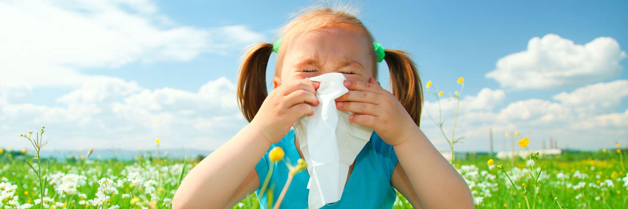 mała dziewczyna dmuchająca nos w chusteczkę - zbliżenie