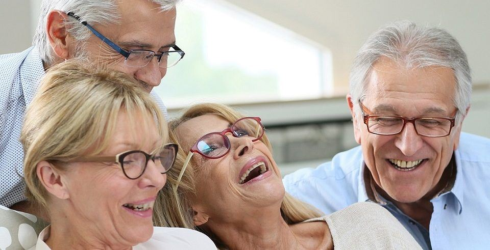 Group of senior friends with eyeglasses using digital tablet