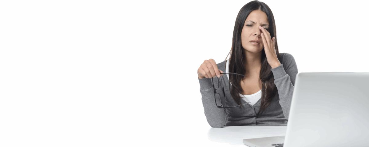 Kobieta siedziąca przy komputerze ze zmęczonymi oczami