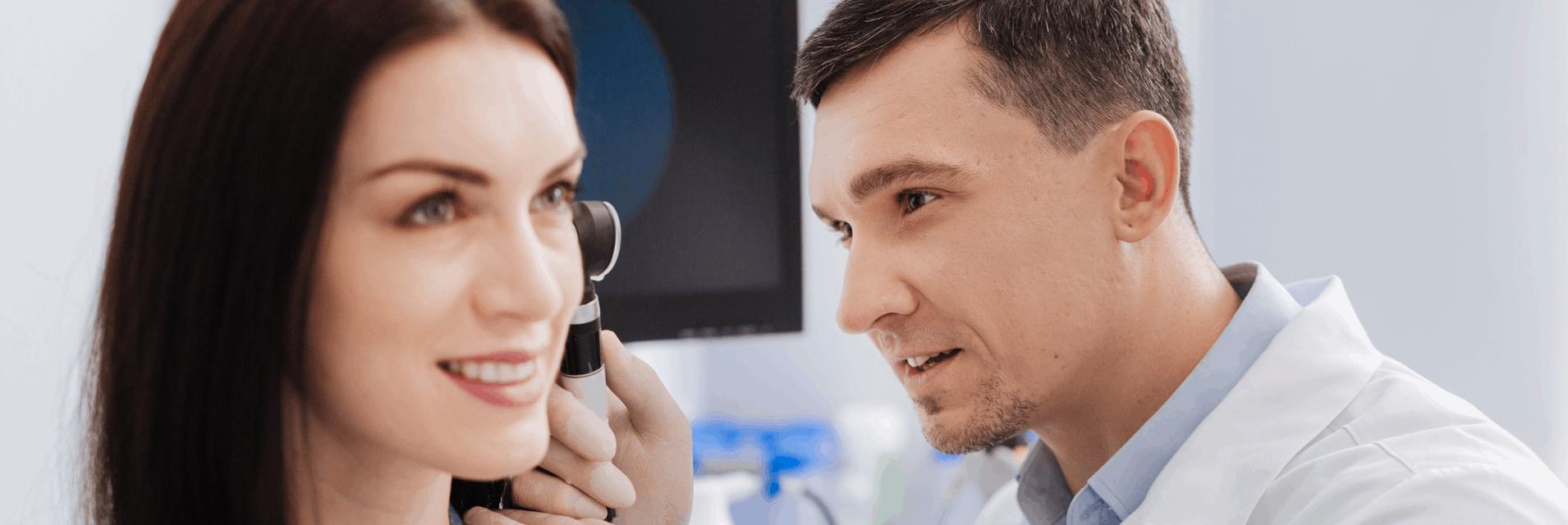Laryngolog badający ucho kobiety w gabinecie specjalistycznym