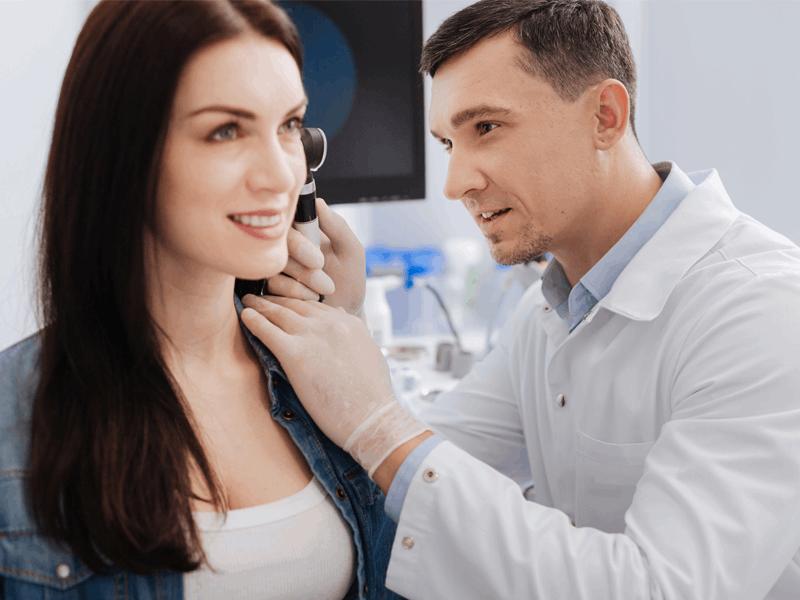 Laryngolog badający ucho kobiety