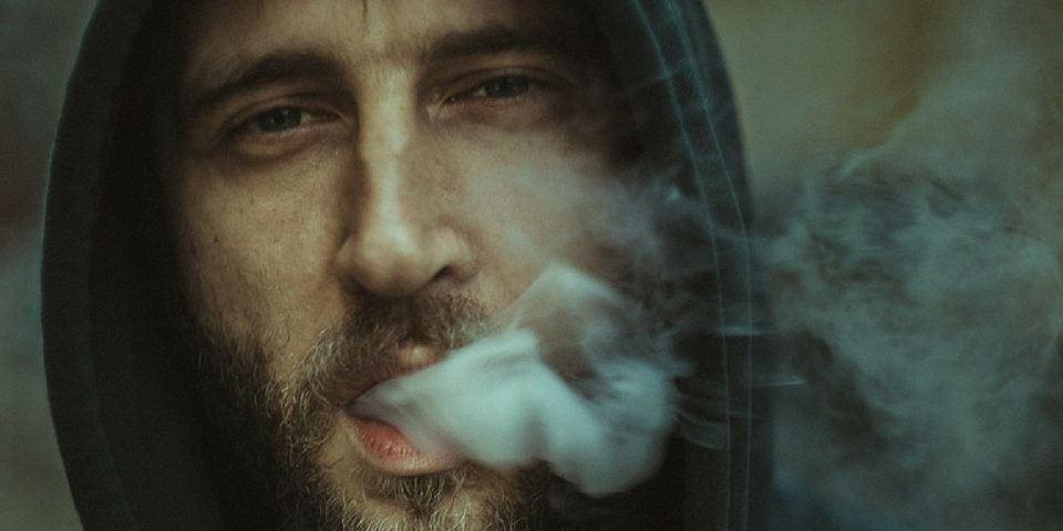 mężczyzna w otoczeniu dymu papierosowego